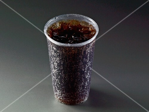 Cola with ice cubes in a plastic cup