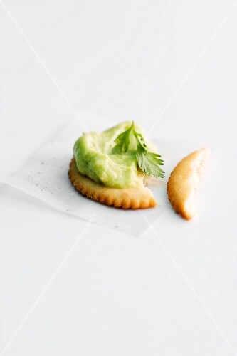 A cracker topped with avocado paste, partly eaten