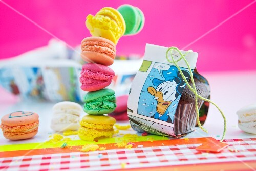 Table decorated for child's birthday party with Donald Duck comic pages and stack of colourful macaroons against pink background