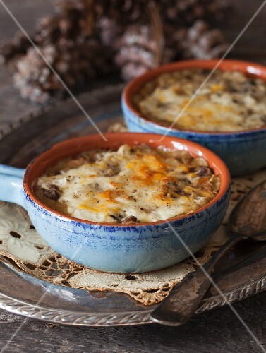 Baked Mushrooms with cheese souce in blue ceramic bowls on a silver tray
