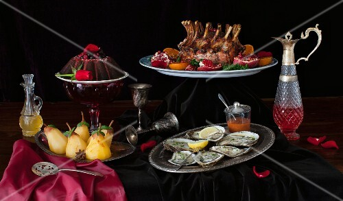 Feastive table with food, crown roast of pork, oysters, chocolate cake and peached pears