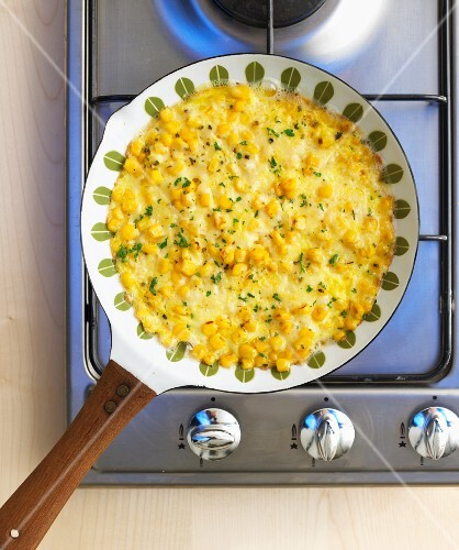 Sweetcorn omelette in a frying pan on a gas hob (view from above)