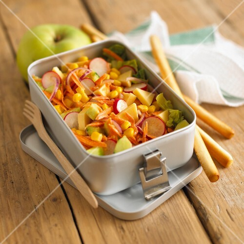 Vegetable salad with sweetcorn, radishes and cheese in a lunch box