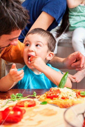 A family baking pizzas: a young boy is nibbling on pizza topping