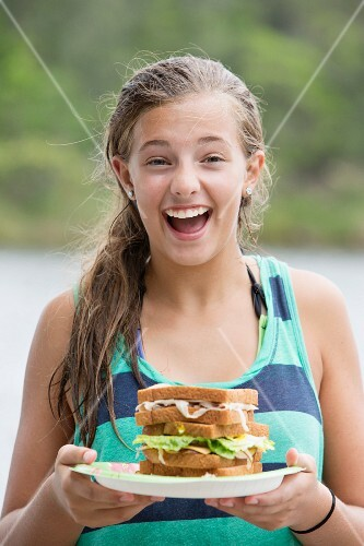 A teenager holding a plate with a multi-tier sandwich