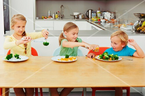 Three children playing with vegetables at a table in the kitchen