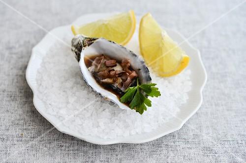 A fresh oyster with lemon wedges on rock salt