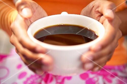 Hände halten eine Tasse Kaffee