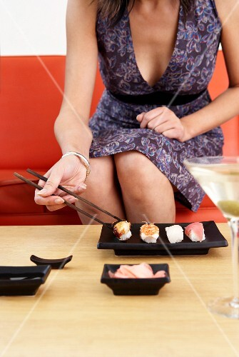 A woman eating sushi, Bangkok, Thailand.