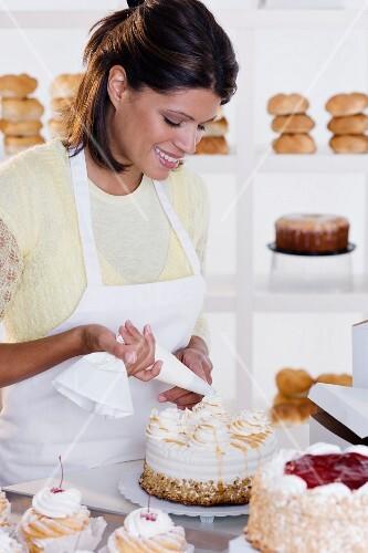 Woman decorating cake at bakery