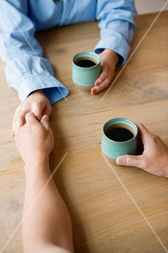 Couple holding hands across the table