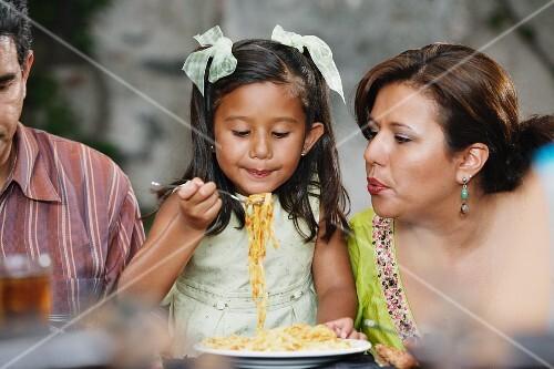 Small girl eating pasta