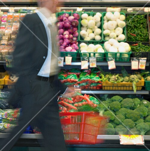Blurry view of man walking by produce in supermarket