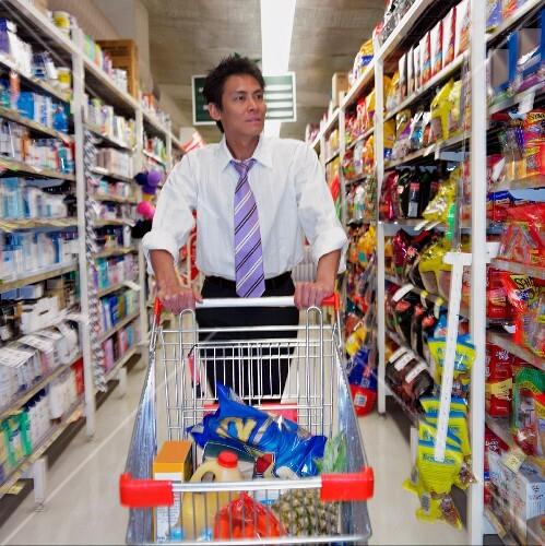 Asian man with shopping cart at supermarket