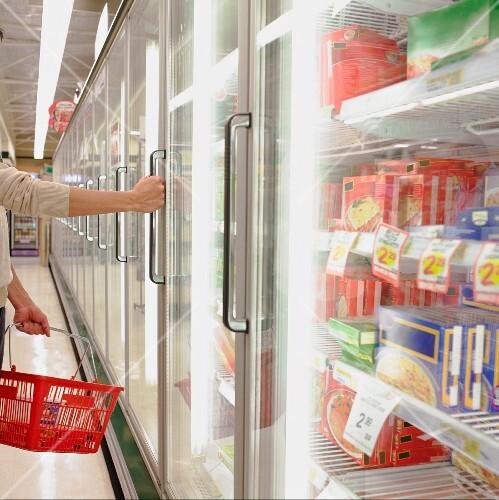 Man opening freezer door at supermarket