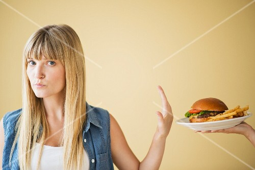 A woman declining a plate of hamburger and chips