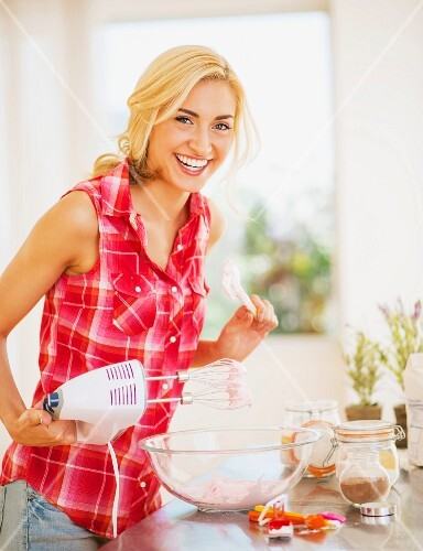A young woman with a hand mixer in the kitchen