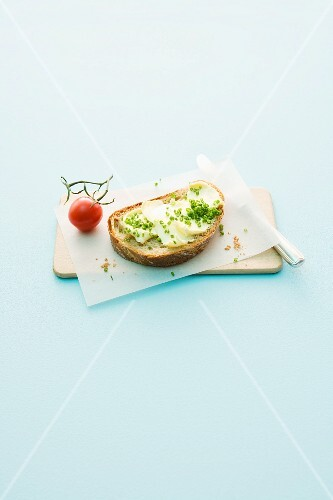 Bread and butter with chives and tomato on a wooden board