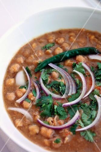 Bowl of chana masala with cilantro, red onion and green chili pepper garnish