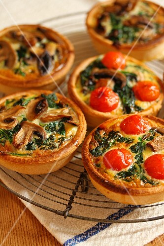 Tartlets with tomatoes, mushrooms and spinach, on a cooling rack