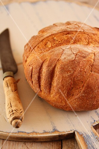 Rustic bread with a knife on a wooden board