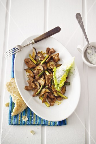 Doner kebab meat with courgette and dill yoghurt on a lettuce leaf