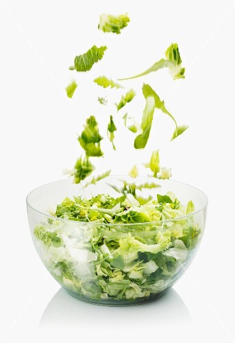 Lettuce leaves falling into a bowl