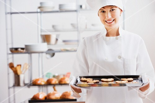 Female pastry chef with tray of cookies