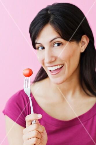 Studio shot of Hispanic woman holding fork with cherry tomato