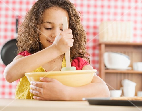 Young girl mixing batter in kitchen