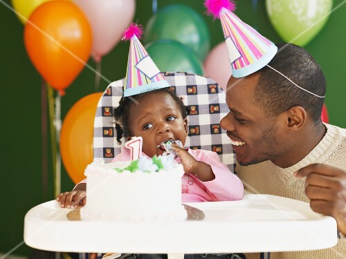 African father and baby in high chair eating birthday cake