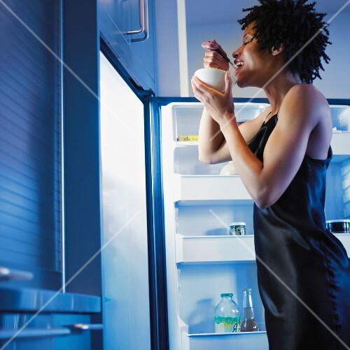 African woman eating next to open refrigerator