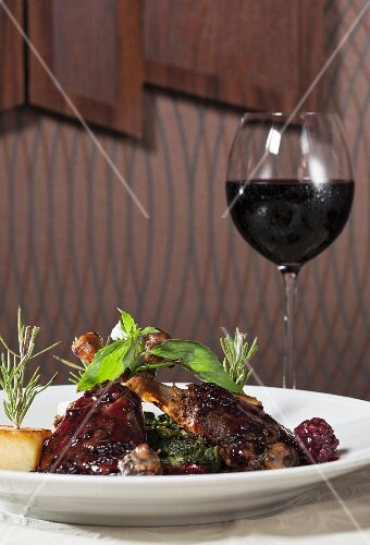 Roasted duck legs with spinach and red wine