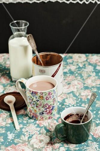 A mug of cocoa, milk and cocoa powder