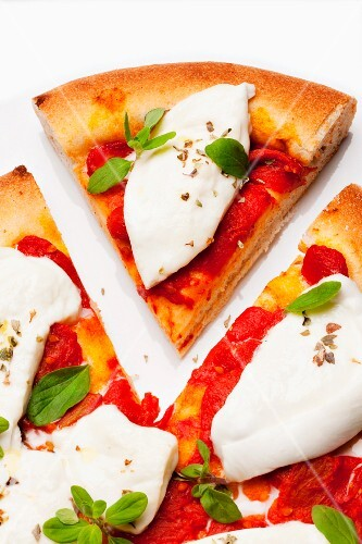 Pizza with buffalo mozzarella, tomatoes and basil, one slice cut