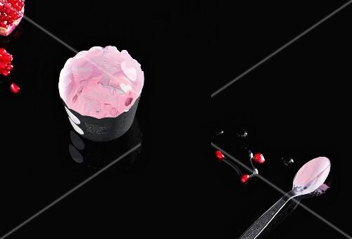 Yogurt and pomegranate seeds on black background