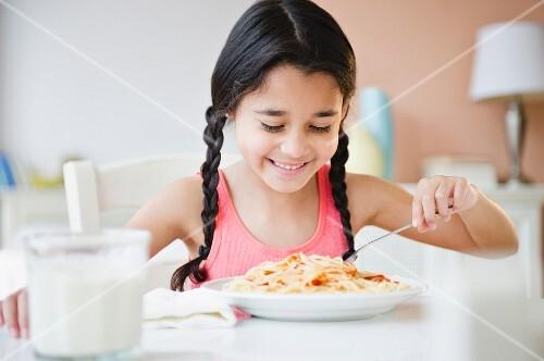 Mixed race girl eating spaghetti
