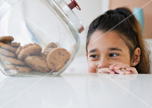 Mixed race girl looking at cookies in cookie jar