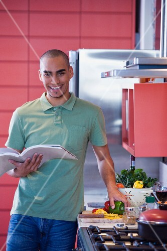 African American man reading cookbook