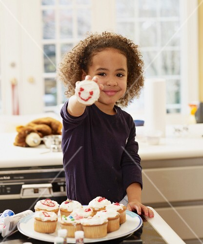 African girl holding decorated cupcake