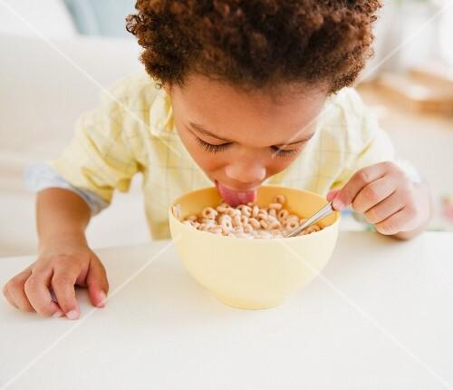 Black boy eating bowl of cereal
