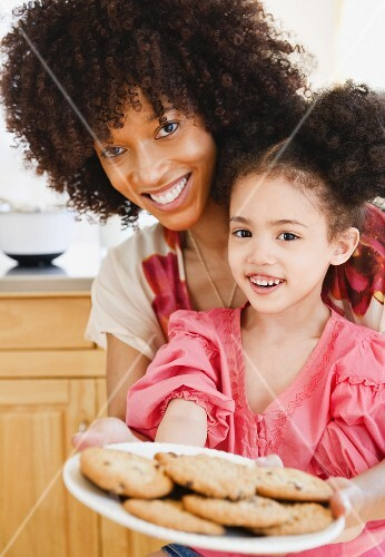 Mother and daughter holding plate of cookies
