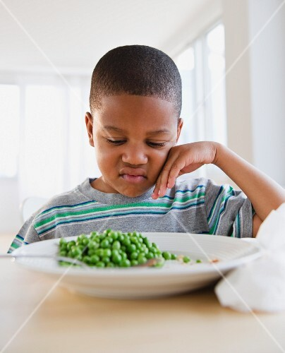 Dunkelhäutiger Junge sitzt unzufrieden vor Teller mit Erbsen