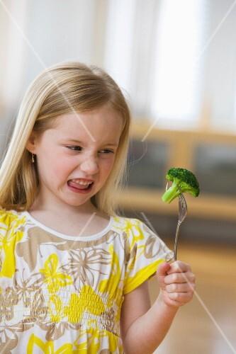 Girl grimacing at broccoli on fork