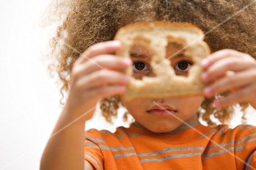 Mixed race boy looking through holes in slice of bread