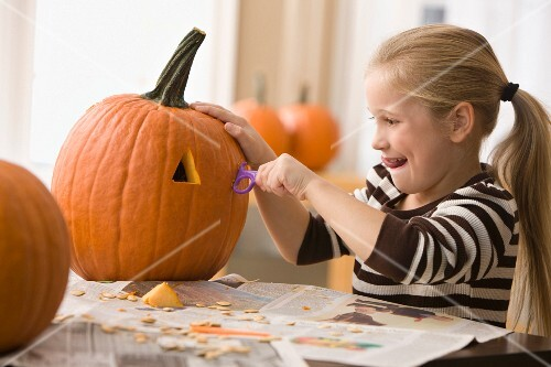 Caucasian girl carving pumpkin