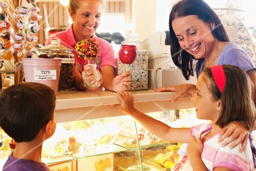Waitress handing candy apple to young girl