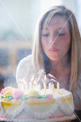 A teenager blowing out candles on a birthday cake