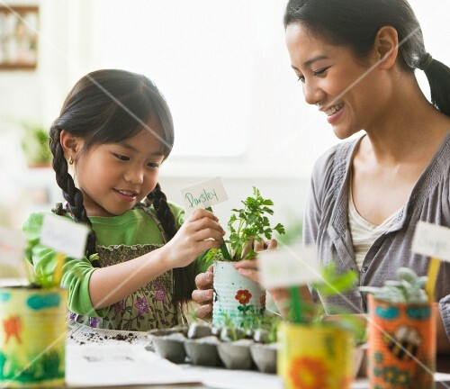 Asian mother and daughter potting plants