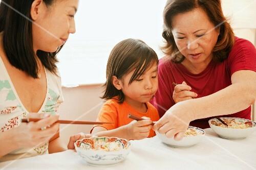 Chinese grandmother teaching grandson to use chopsticks